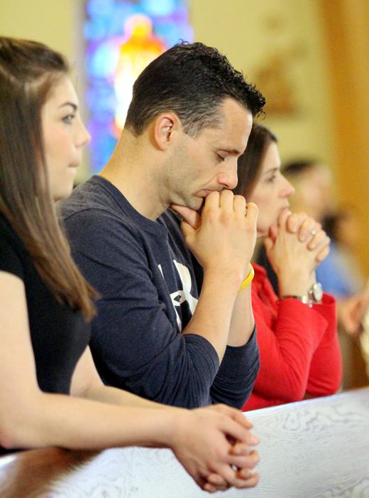 Alex Hyduke, Fred Sylvester and Leslie Sylvester pray during the Liturgy of the Eucharist at St. Thomas More Church.