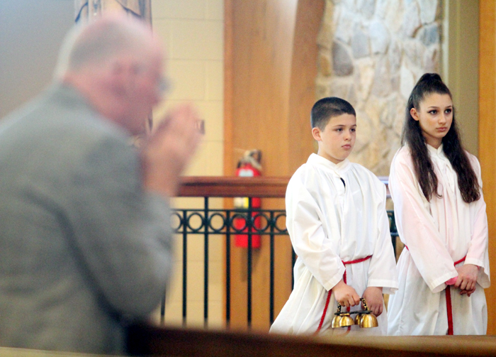 Siblings Aidan and Elise Sylvester serve the 5:30 mass on Saturday evening at St. Thomas More Church.