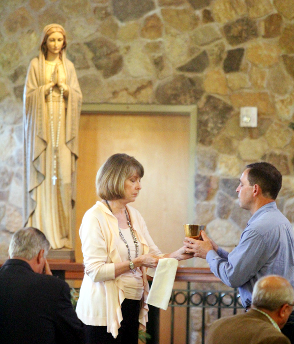 Judy Davis distributes the Blood of Christ.
