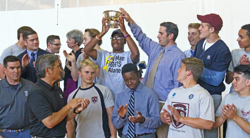 Members of the St. Joseph's Preparatory School rugby team hoist the Hurtado Cup, a school distinction in an intramural competition to raise the most money for a designated charitable cause. (Photo by Sarah Webb)