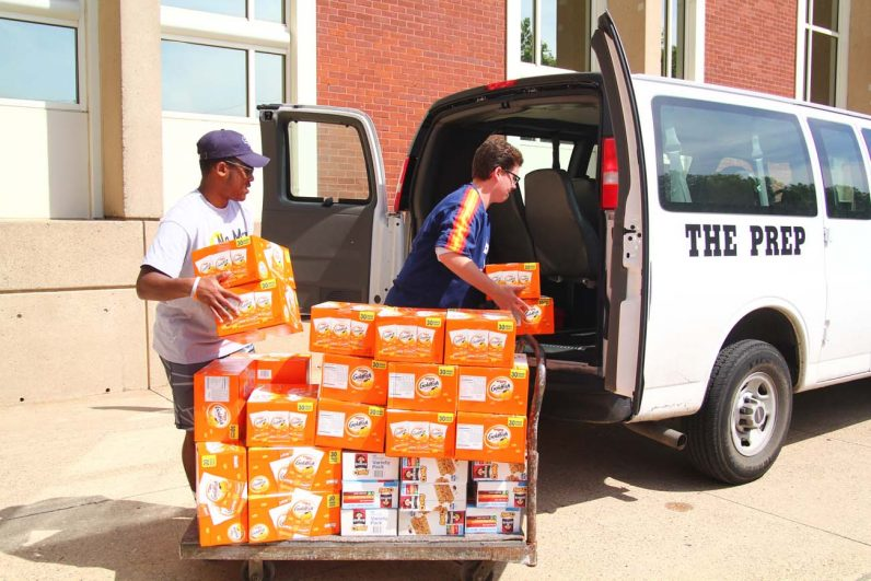 Rugby player Xavier Steward and Pat Gellespie, president of St. Joseph's Prep Hurtado Food Pantry, load up snacks for delivery to Germantown's Face to Face.
