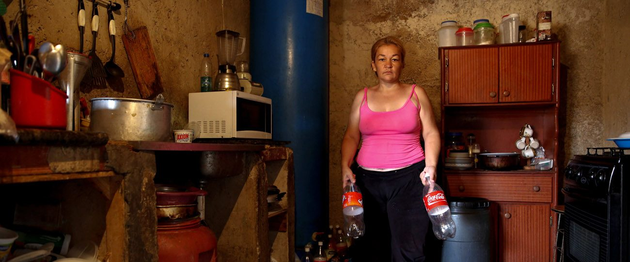 Yunni Perez holds plastic bottles used to carry water while she poses for a photo April 3 inside her home in a slum area of Caracas, Venezuela. (CNS photo/Carlos Garcia Rawlins, EPA)