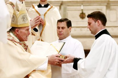 Kyle Adamczyk (right), a Second Theology seminarian studying for the Philadelphia Archdiocese, receives the ministry of acolyte from Bishop David O'Connell. With reception of the ministry, Adamczyk is on track to be ordained a transitional deacon next year, and eventually a priest in 2018. (Sarah Webb)