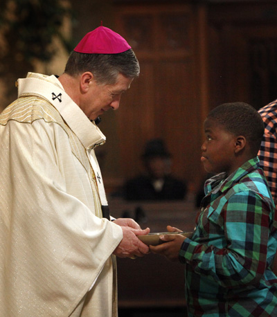 Dominic Banks hands the offertory gifts to Chicago Archbishop Blase J. Cupich during a Mass for peace at St. Martin de Porres Church on the city's west side. The archbishop visited to offer support for parishioners' efforts to build peace in their violent neighborhood. (CNS photo/Karen Callaway, Catholic New World)