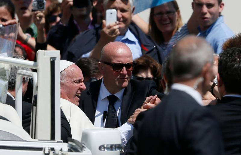 Pope Francis reacts as someone in the crowd pulls his hand as he leaves his general audience in St. Peter's Square at the Vatican May 4. Domenico Giani, center, the pope's lead bodyguard, intervenes. (CNS photo/Paul Haring)