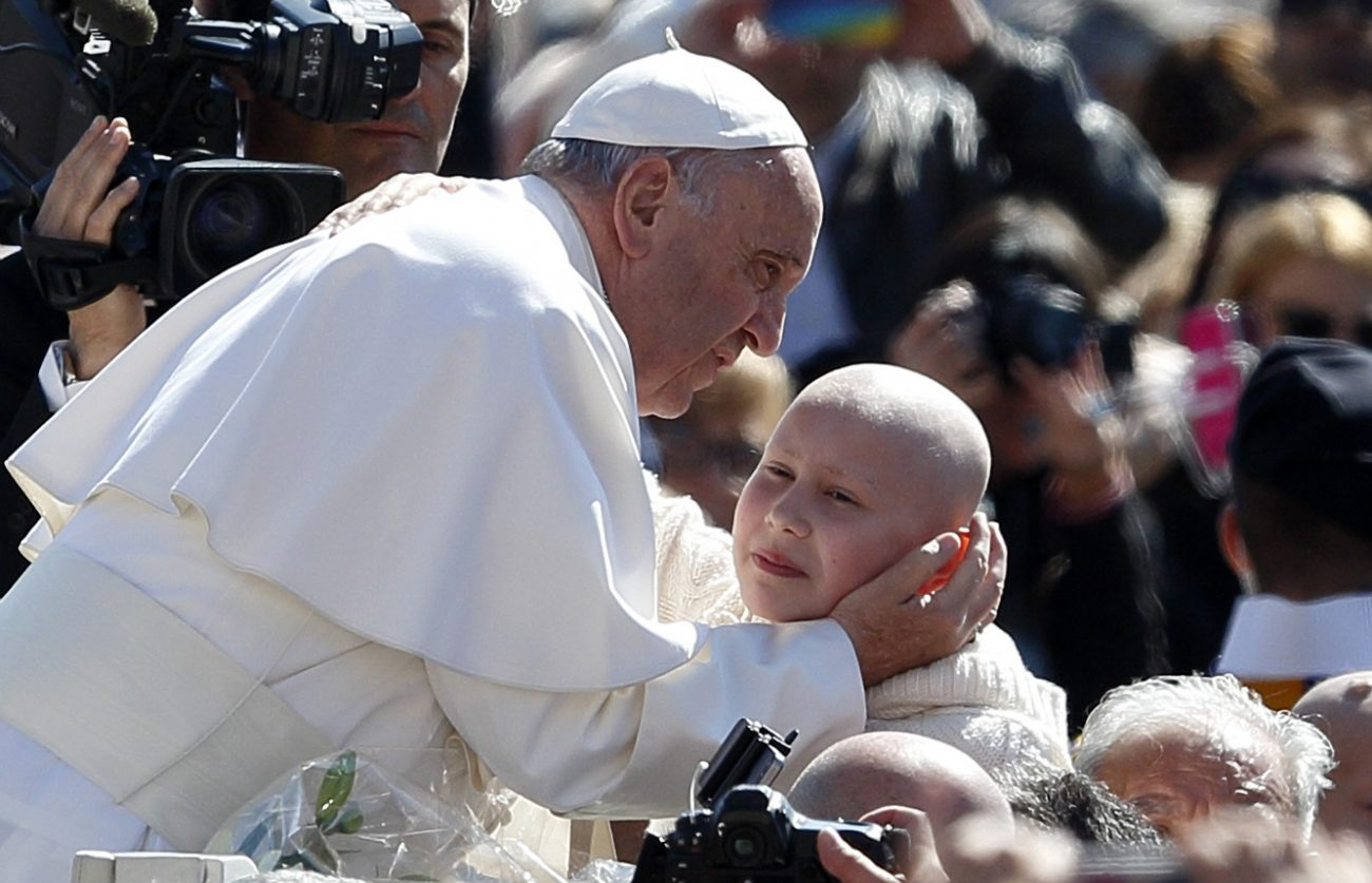Pope Francis greets a young person during his general audience in St. Peter's Square at the Vatican May 18. (CNS photo/Paul Haring)