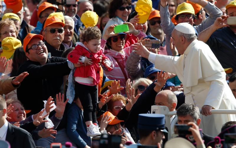 Pope Francis greets a child during a special audience for military members and their families in St. Peter's Square at the Vatican April 30. (CNS photo/Paul Haring)