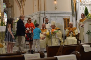 Archbishop Charles Chaput accepts a gift from a family of St. John the Baptist Parish at the close of the Mass April 24. (Roseanne Westerfer)