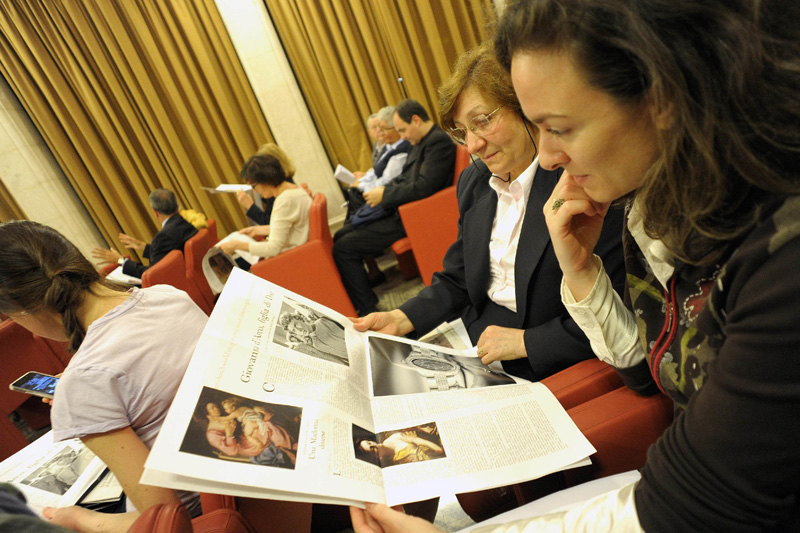 "Women look at a monthly women's insert called ""Women-Church-World"" in the Vatican's L'Osservatore Romano newspaper in this May 30, 2012, file photo. The newspaper insert has now turned into a monthly magazine with the same name. (CNS photo/L'Osservatore Romano via Reuters)"