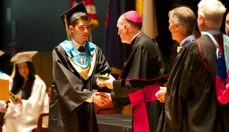 A Neumann-Goretti senior receives his diploma from Auxiliary Bishop Michael Fitzgerald. (Bradley Digital)