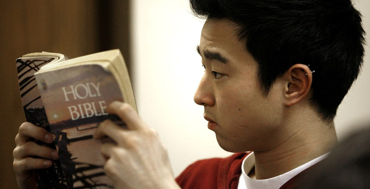A young man is seen reading a Bible in 2010. A new State of the Bible Survey by the American Bible Society found that 77 percent of Catholics want to read the Bible more often. (CNS photo/Karen Callaway, Catholic New World)