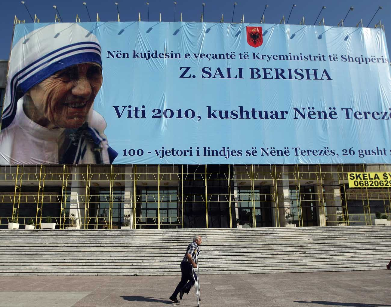 A man on crutches passes a large banner of Blessed Teresa of Kolkata in 2010 in Tirana, Albania. Mother Teresa, founder of the Missionaries of Charity who won the Nobel Peace Prize in 1979, will become a saint Sept. 4. (CNS photo/Armando Babani, EPA)