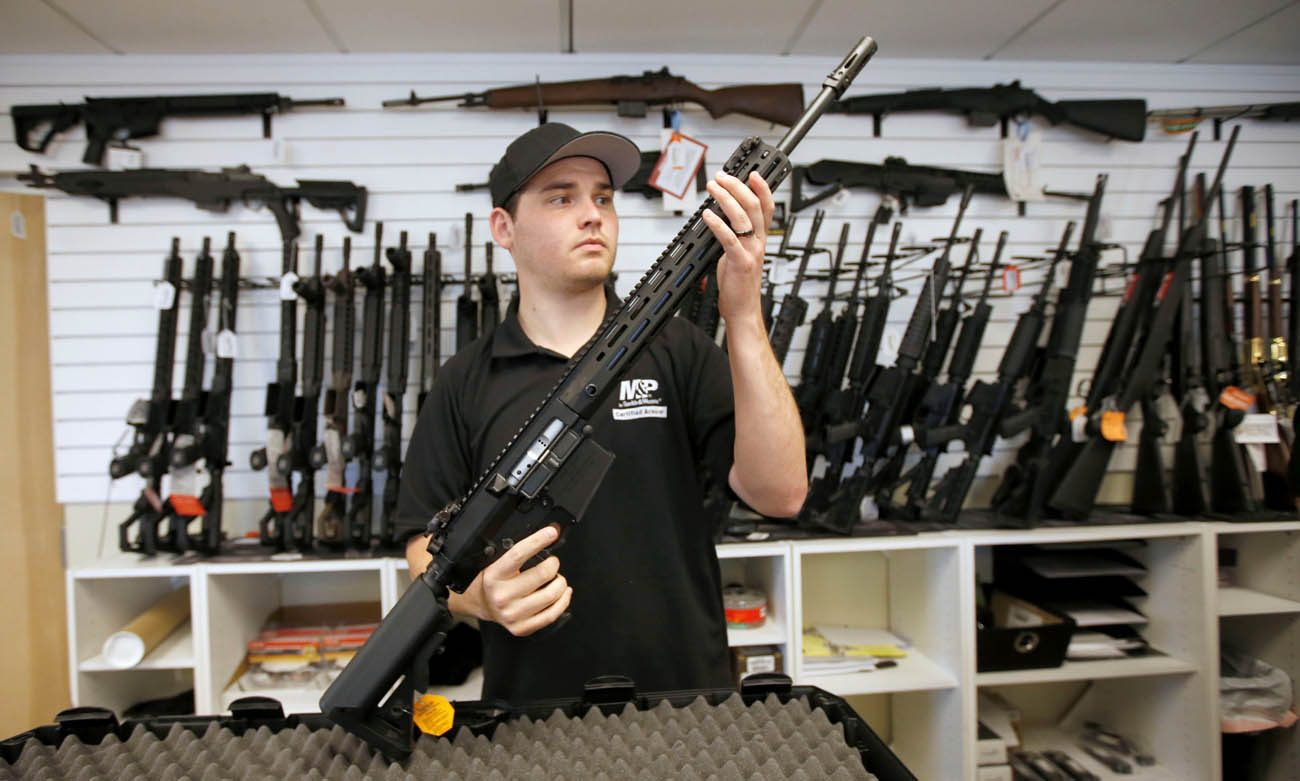 Salesman Ryan Martinez inspects a new AR-10 at the Ready Gunner gun store in Provo, Utah. Two U.S. Catholic prelates called for a ban on the sale of military-style assault weapons, saying they have no place in the hands of civilians. (CNS photo/George Frey, Reuters)