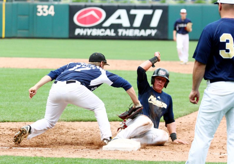 A Catholic League base runner makes it back safely to first base.