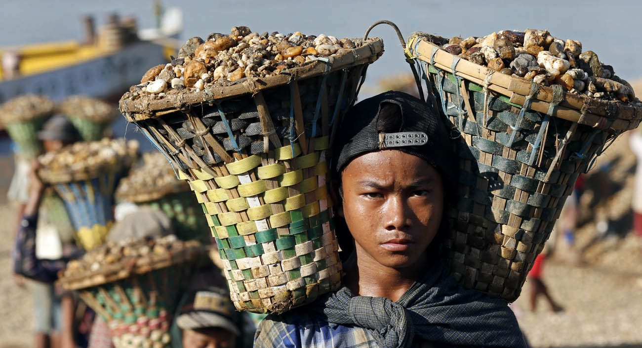 Children in Yangon, Myanmar, carry baskets loaded with gravel used for construction, Nov. 6, 2015. Pope Francis called on the world community June 12 to come together to eliminate the root causes that force millions of children into the world of slave labor. (CNS photo/Rungroj Yongrit, EPA)