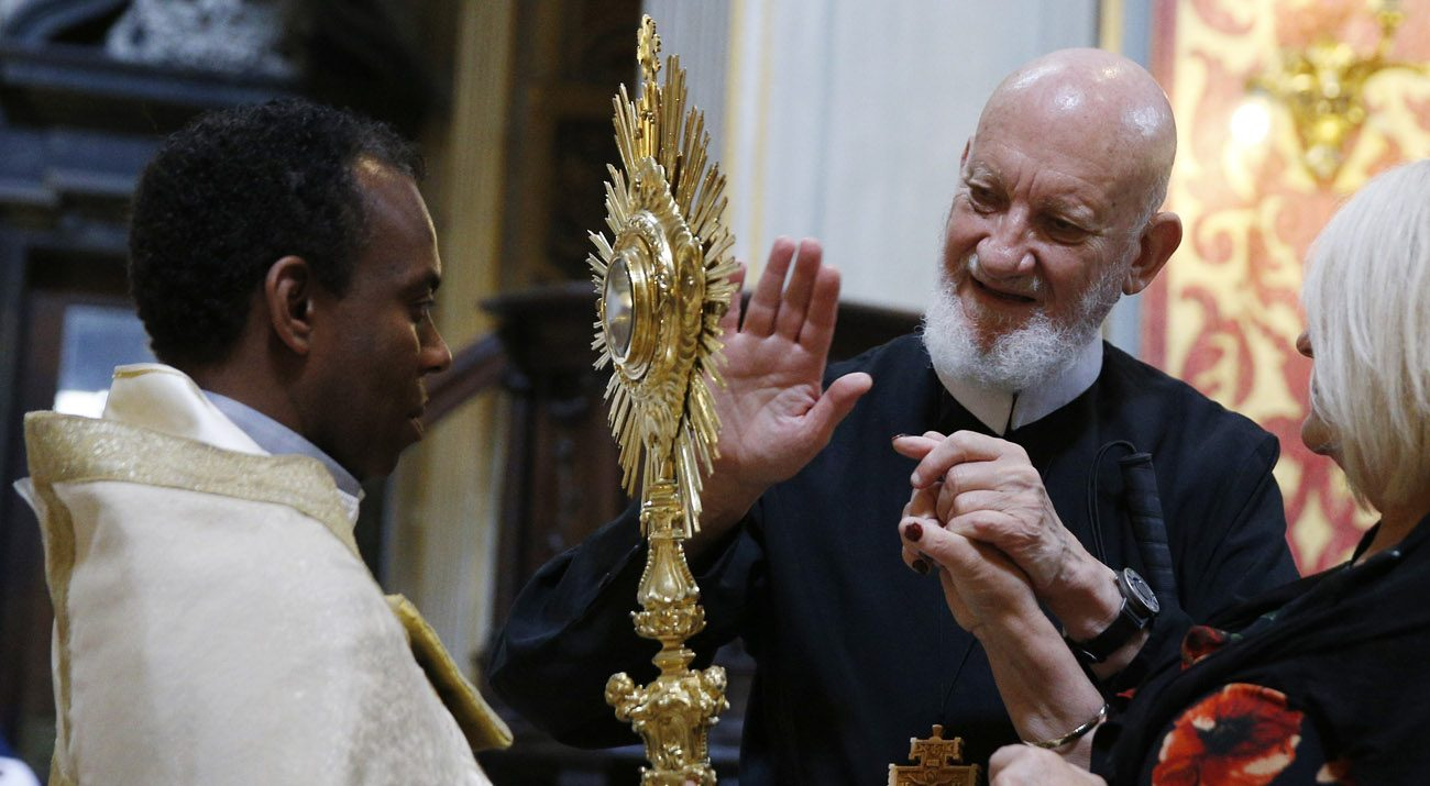 Redemptorist Father Cyril Axelrod, who is deaf and blind, touches a monstrance during exposition of the Eucharist at Chiesa Nuova in Rome June 10.  (CNS photo/Paul Haring)