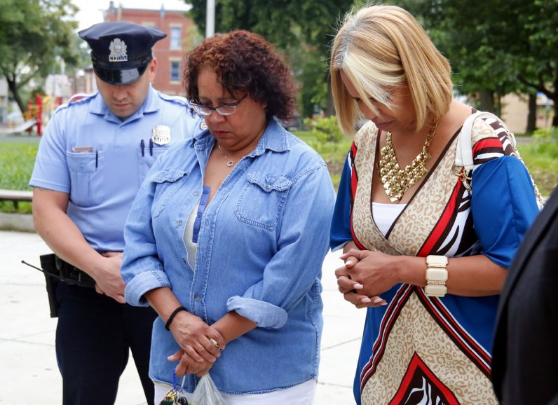 A police officer joins community members in prayer at Fairhill Square Park in North Philadelphia.