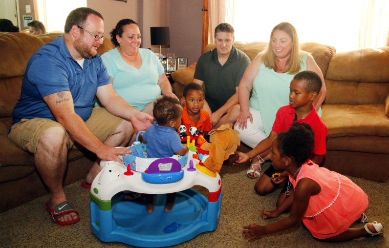 """Enjoying some time together at the Darrah home are (seated, from left) Michael and Nicole Darrah, Matthew and Lou Ann Feuerstein and their children playing on the floor, in red, Jude 5, James 6, and Zoe 5, along with baby """"Jay"""" in his jumper."""