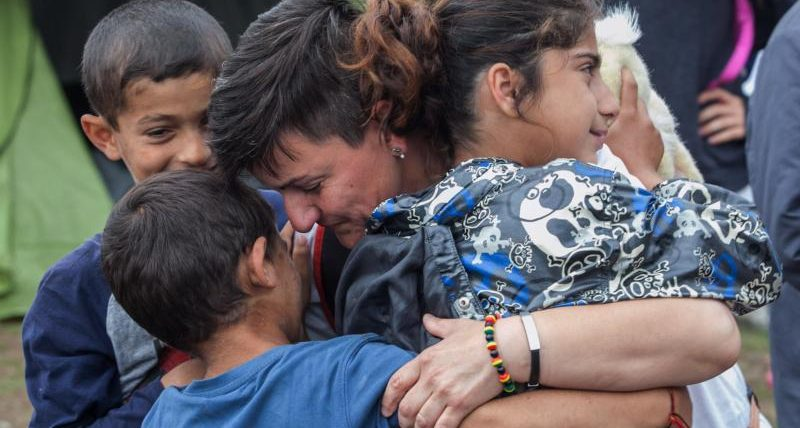 A volunteer from a humanitarian organization hugs refugee children June 13 during a police operation at a makeshift camp in Polykastro, Greece. (CNS photo/Nikos Arvantidis, pool via EPA)