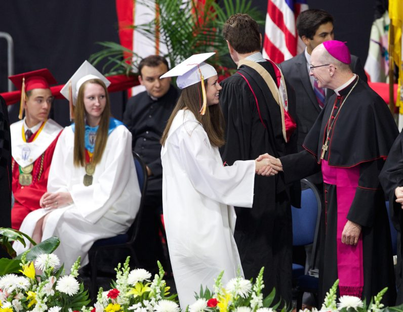 Bishop Timothy Senior congratulates a student from Archbishop John Carroll High School at Cabrini College on Thursday, June 2. (Joe Bradley)
