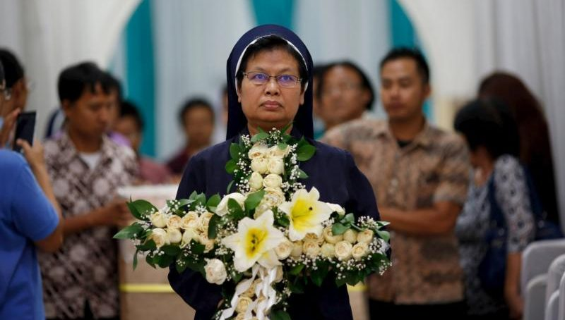 A religious sister carries a cross made of flowers during a funeral in Jakarta, Indonesia, May 1, 2015. (CNS photo/Nyimas Laula, Reuters)