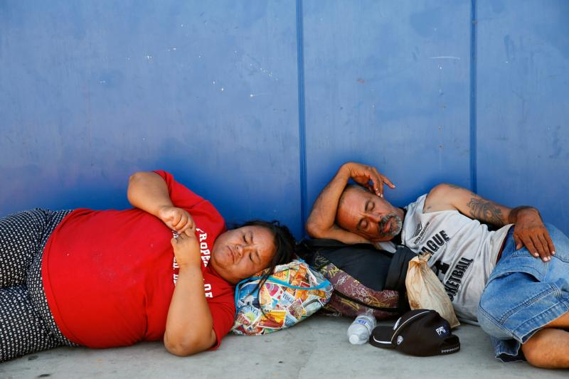 Corina Cristan, left, naps alongside an unidentified man in a strip of shade outside the main dining hall of the Society of St. Vincent de Paul in Phoenix June 14. Phoenix temperatures are expected to reach all-time highs this summer putting the homeless and others at greater risk for heat-related illness. (CNS photo/Nancy Wiechec)