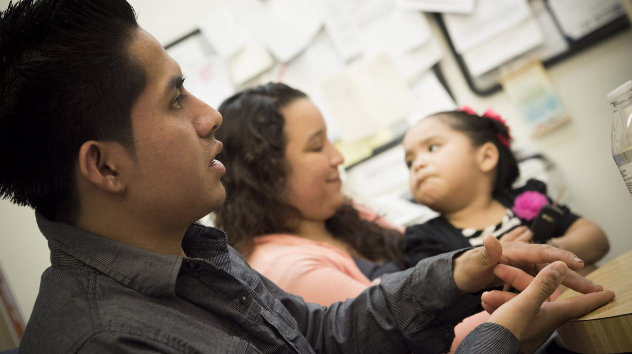 Jose Aguilar, seen with his wife and daughter, sits for an interview. He was a child when he and his family entered the United States without legal permission. A Catholic Charities program in Trenton, N.J., helped him attain legal status through the Deferred Action for Childhood Arrivals program. (CNS photo/Jeff Bruno, The Monitor)