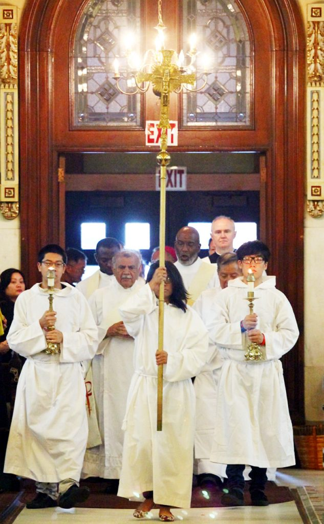 Altar servers lead the procession of deacons, priests and Archbishop Charles Chaput into St. Thomas Aquinas Church.