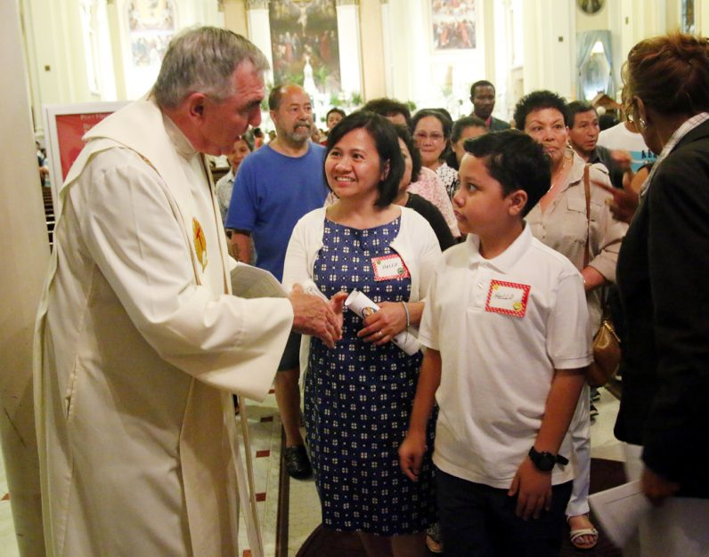 Msgr. Hugh J. Shields, pastor of St. Thomas Aquinas Parish, greets Cristine and Bryan Jumarang after the service.