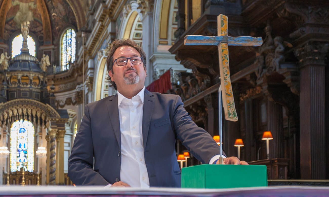 Italian carpenter Francesco Tuccio is pictured in London's St. Paul's Cathedral with a cross he made from pieces of a boat that wrecked in 2013 off the coast of Lampedusa, Italy. The British Museum commissioned the weather-beaten cross displayed at the cathedral, and it now holds a prominent place in the museum in London. (CNS photo/Graham Lacdao,  Chapter of St Paul's)