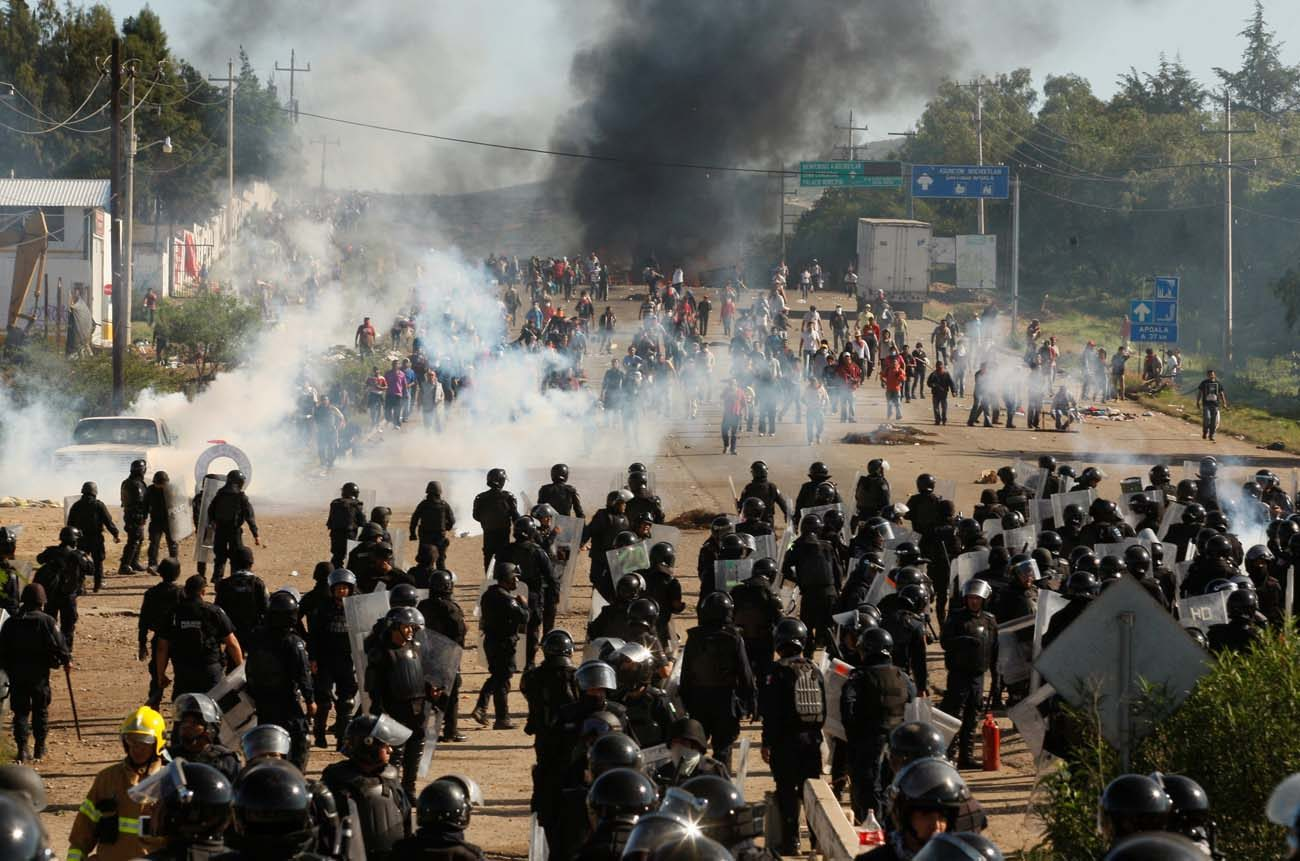 Protesters from a national teachers union clash with riot police in Nochixtlan, Mexico, during a June 20 protest against President Enrique Pena Nieto's education reform. Violent clashes between police and members of the teachers union, who had blockaded roads in southern Mexico, left at least eight people dead and more than 100 injured, officials said. (CNS photo/Jorge Luis Plata, Reuters)