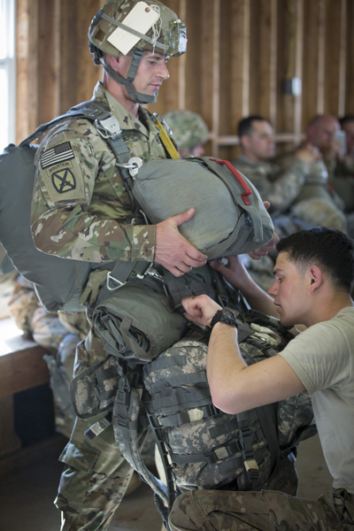 A jump master checks the parachute worn by Father Lukasz J. Willenberg March 9 at Camp Mackall Army Base in Southern Pines, N.C., shortly before he jumped out of an airplane during a military training exercise. Father Willenberg, who holds the rank of captain, is a U.S. Army chaplain at Fort Bragg in Fayetteville, N.C., and trains as a noncombat paratrooper with the 82nd Airborne Division. (CNS photo/Chaz Muth)