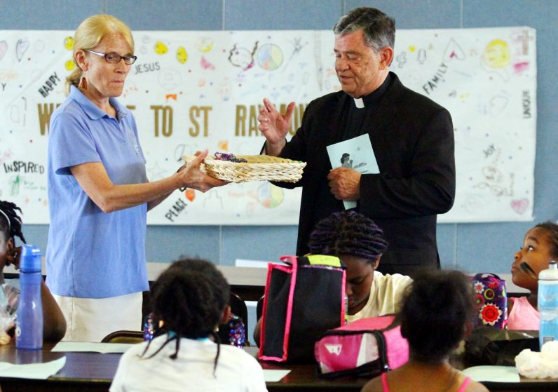 Msgr. Daniel Sullivan blesses necklaces and chains that will be given to the children as a symbol of their peace pledge.