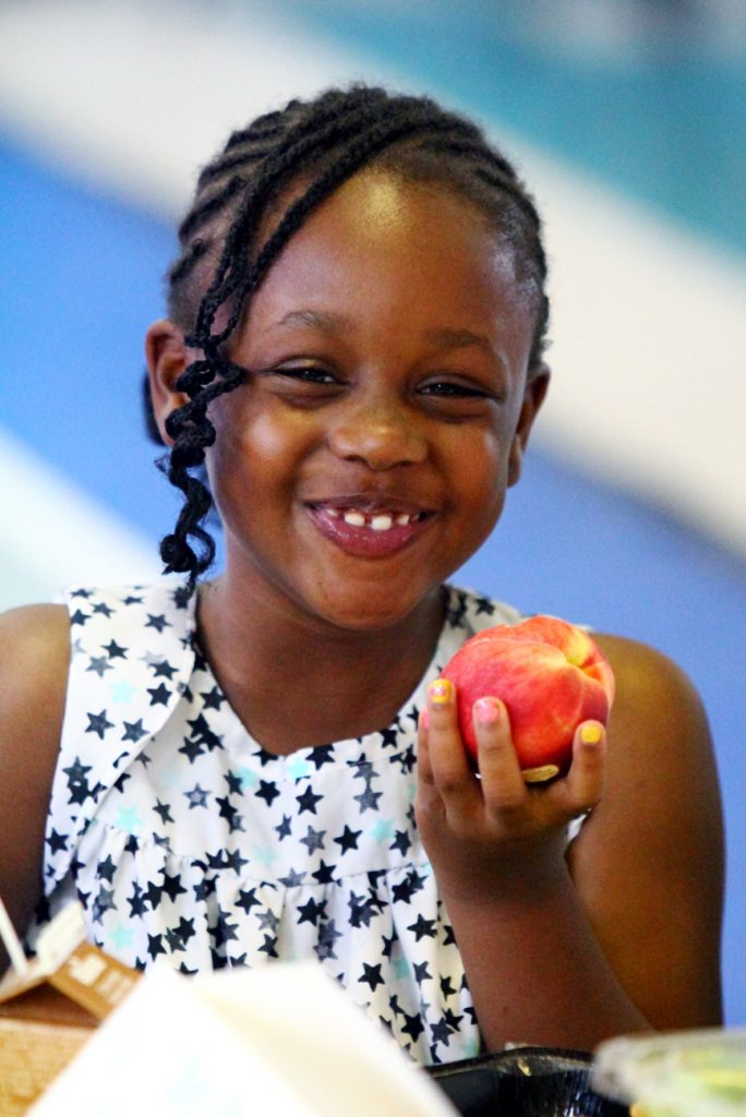 Kennedy Patillo enjoys the peach in her lunch provided by NDS' summer meals program.