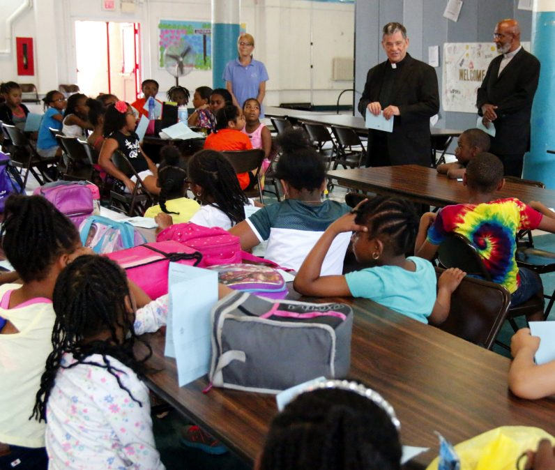 Msgr. Daniel Sullivan (center) speaks to children at St. Raymond School along with Deacon William Bradley and Anne Ayella of Nutritional Development Services.