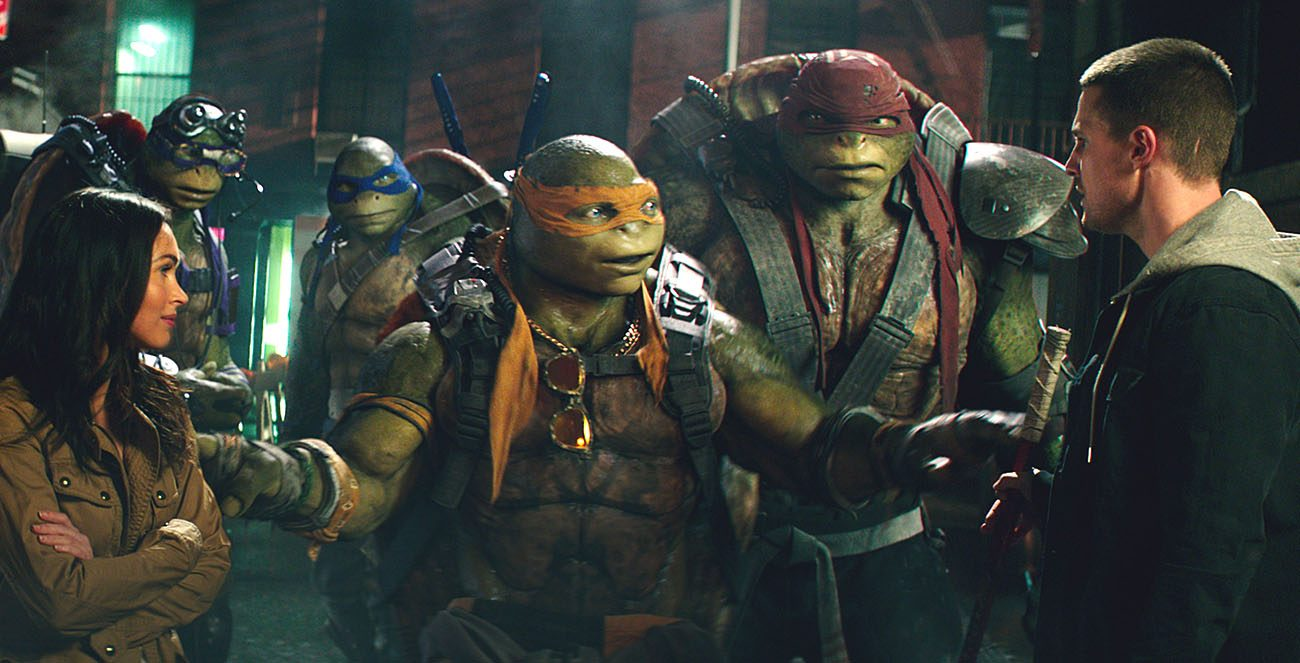 "Megan Fox and Stephen Amel appear with animated characters Donatello, Leonardo, Michelangelo and Raphael in the movie ""Teenage Mutant Ninja Turtles: Out of the Shadows."" (CNS photo/Paramount)"