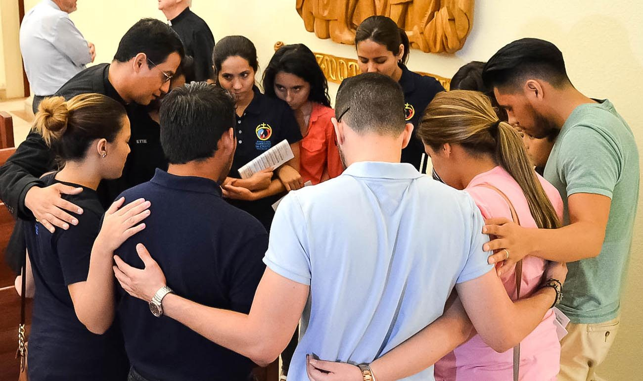 "Father Jorge Torres, director of vocations for the Diocese of Orlando, Fla., prays with young people who participated in the ""Vigil to Dry Tears"" June 13 at St. James Cathedral in Orlando. Father Torres is among the Orlando diocesan priests lending a hand in counseling families and friends of victims of the June 12 massacre at Pulse nightclub in Orlando. (CNS photo/Andrea Navarro, Florida Catholic)"