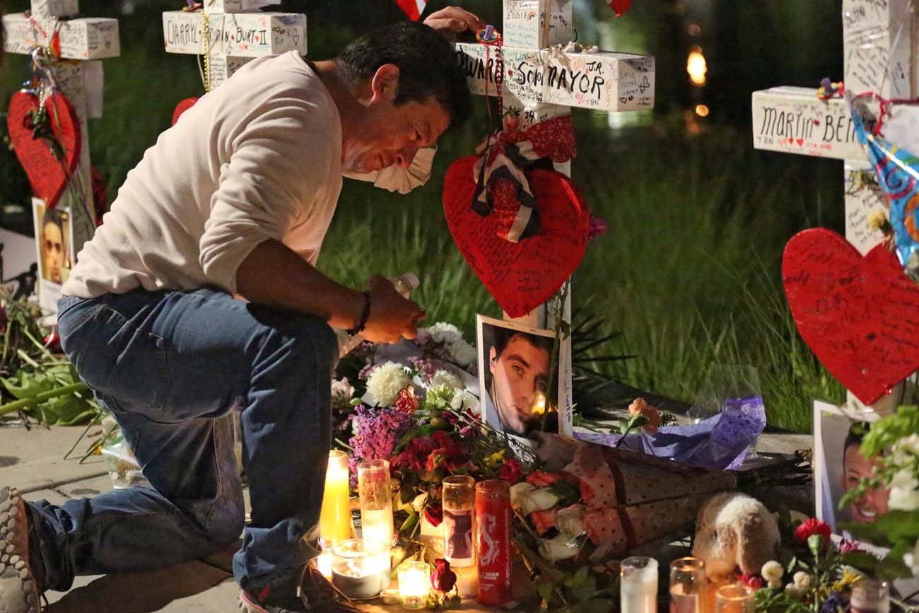 Jose Louis Morales cries as he kneels June 21 at a makeshift memorial for his brother Edward Sotomayor Jr. and other victims of the Pulse night club shootings in Orlando, Fla. (CNS photo/Carlo Allegri, Reuters)