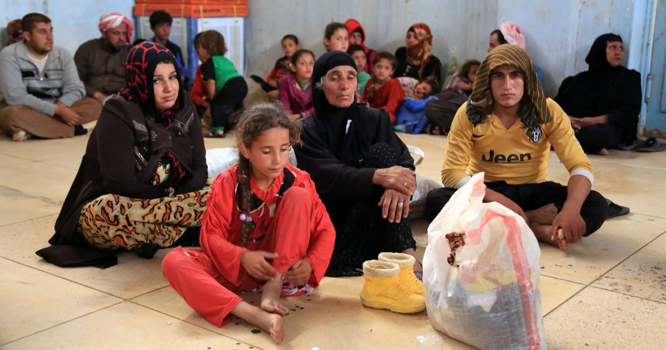 Displaced families await temporary shelter in Kirkuk, Iraq, June 11. Catholic and Orthodox patriarchs called for the rapid liberation of areas under control of the Islamic State group to end ethnic and religious genocide. (CNS photo/Stringer, EPA)