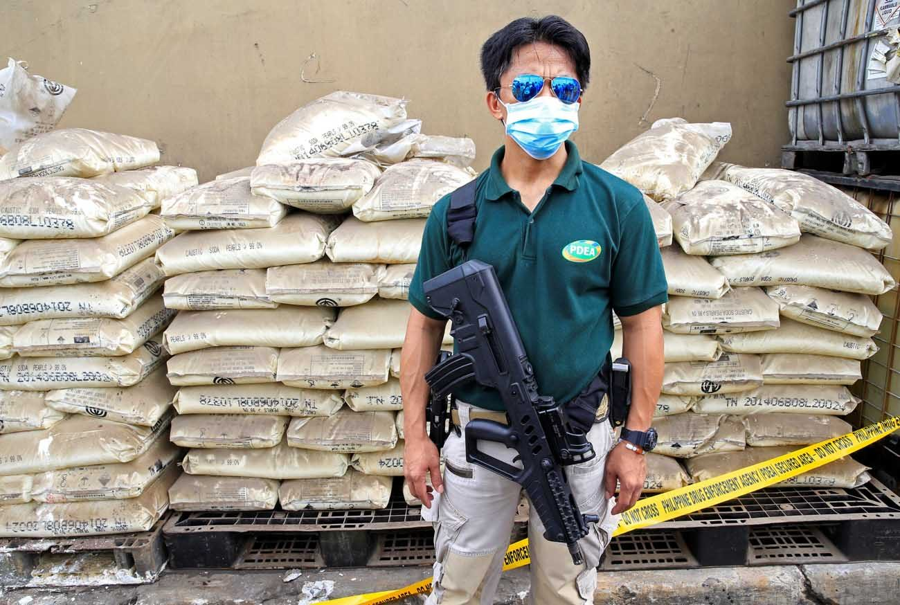 An agent of the Philippine Drug Enforcement Agency stands guard June 16 in front of chemicals used in the production of crystal meth, or Shabu, near Manila, Philippines. Philippine church leaders expressed words of caution in the wake of recent killings of suspected criminals, after voters there elected Rodrigo Duterte, who ran for president on the promise to rid the country of crime during his first six months in office. (CNS photo/Romeo Ranoco, Reuters)