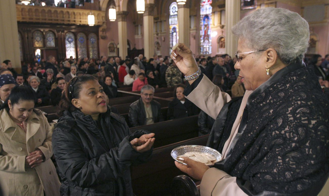 A eucharistic minister distributes Communion during a 2008 Mass at Transfiguration Church in the Williamsburg section of Brooklyn, N.Y. (CNS photo/Gregory A. Shemitz)