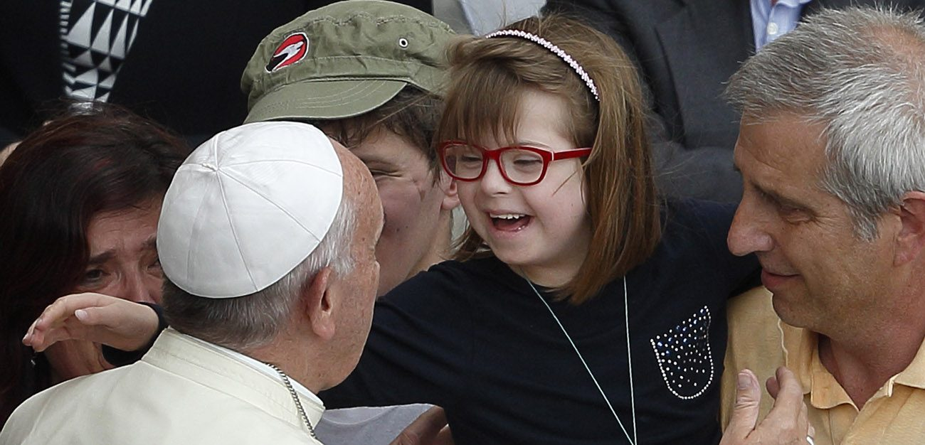 Pope Francis greets a girl after celebrating a Mass for the sick and disabled in St. Peter's Square at the Vatican June 12. The Mass was an event of the Jubilee of Mercy. (CNS photo/Paul Haring)