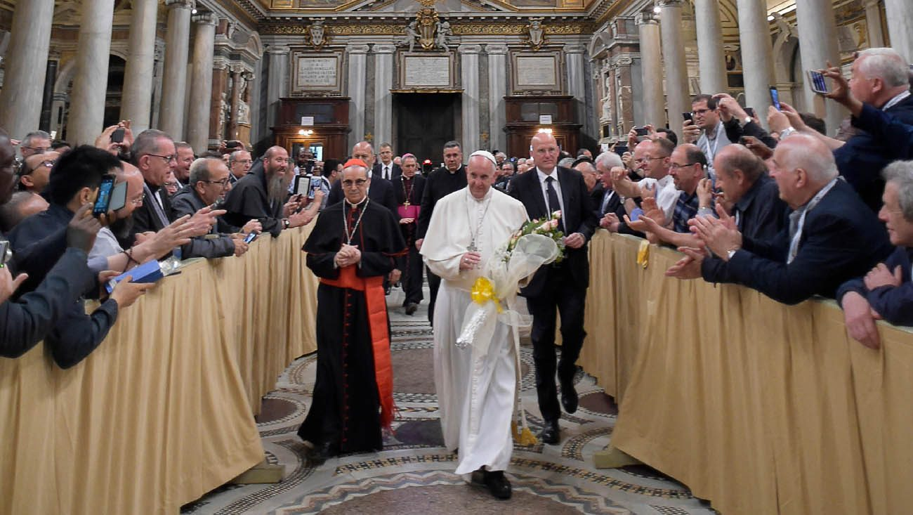 "Pope Francis carries a bouquet of flowers as he arrives to give a talk at a retreat for priests at the Basilica of St. Mary Major in Rome June 2. The pope placed the flowers in front of the Marian icon, ""Salus Populi Romani,"" (health of the Roman people). Walking next to the pope is Cardinal Santos Abril Castello, archpriest of the basilica. (CNS photo/L'Osservatore Romano, handout)"
