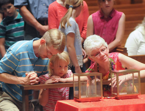 Nole German prays as his daughter Ella, 9, and Peggy Imholte, view the relics of St. Thomas More and St. John Fisher June 27 at the St. Mary's Cathedral in St. Cloud, Minn. The relics of the two saints are on a national tour. (CNS photo/Dianne Towalski, The Visitor) See RELICS-SAINTS-CROWDS June 29, 2016.