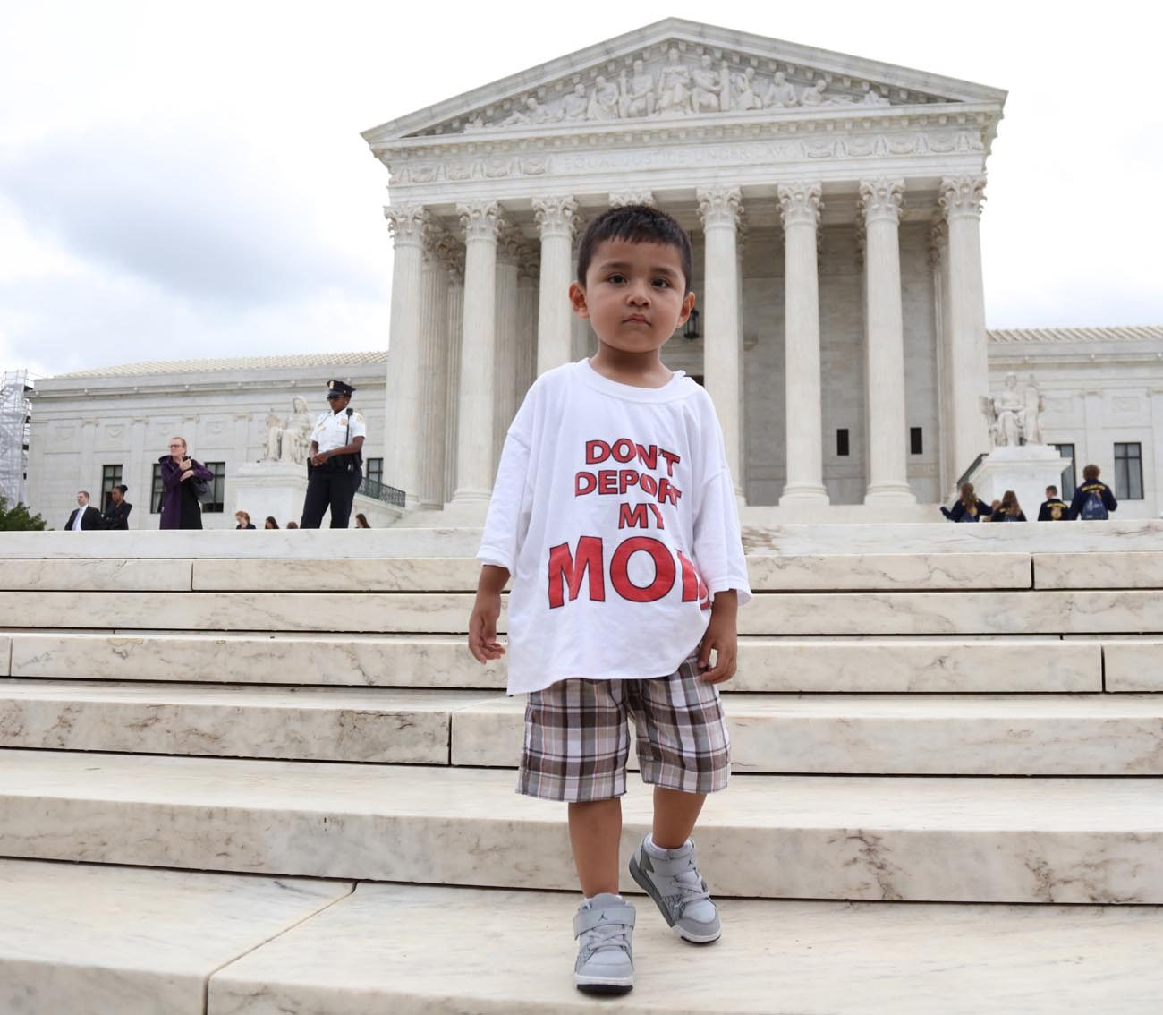 "A boy wearing a T-shirt reading ""Don't Deport My Mom"" stands outside the U.S. Supreme Court in Washington June 23 after the justices issued a 4-4 ruling on President Barack Obama's executive actions on immigration. The split decision leaves in place a lower court ruling that blocked Obama's policies. (CNS photo/Andrew Gombert, EPA)"