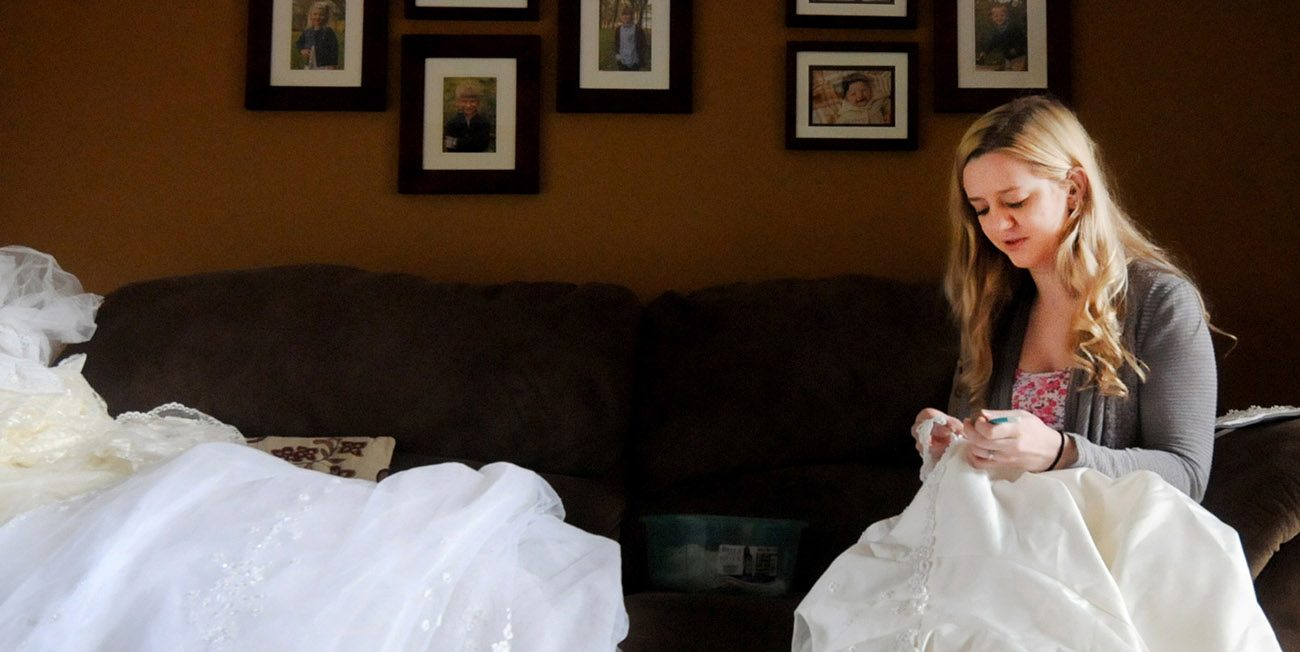 Sarah Novak does the delicate work of taking apart donated wedding dresses April 27 at her home in Rice, Minn., so the material can be reused to make garments to give families grieving the loss of a child. (CNS photo/Dianne Towalski, The Visitor)