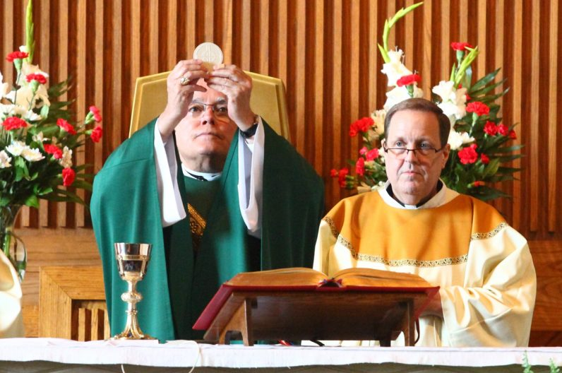 Father William Lange (right), pastor of Sacred Heart Parish, concelebrates the Mass with Archbishop Chaput.