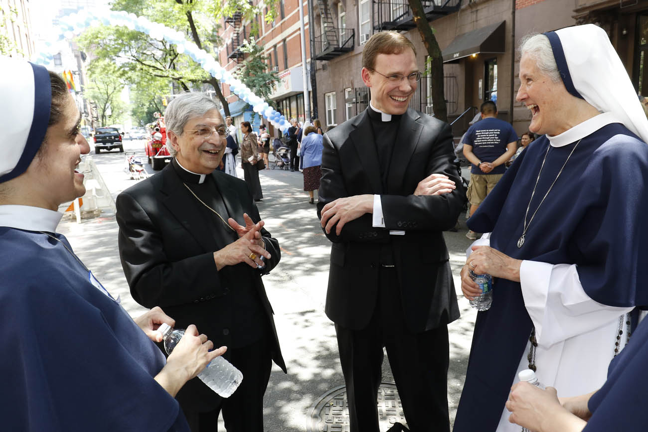 Bishop Salvatore R. Matano, left, of Rochester, N.Y., and Father Daniel White chat with Sister Mariam Caritas, immediate left, and Mother Agnes Mary Donovan, superior general of the Sisters of Life, during a block party in New York City June 1 celebrating the religious community's 25th anniversary. (CNS photo/Gregory A. Shemitz)