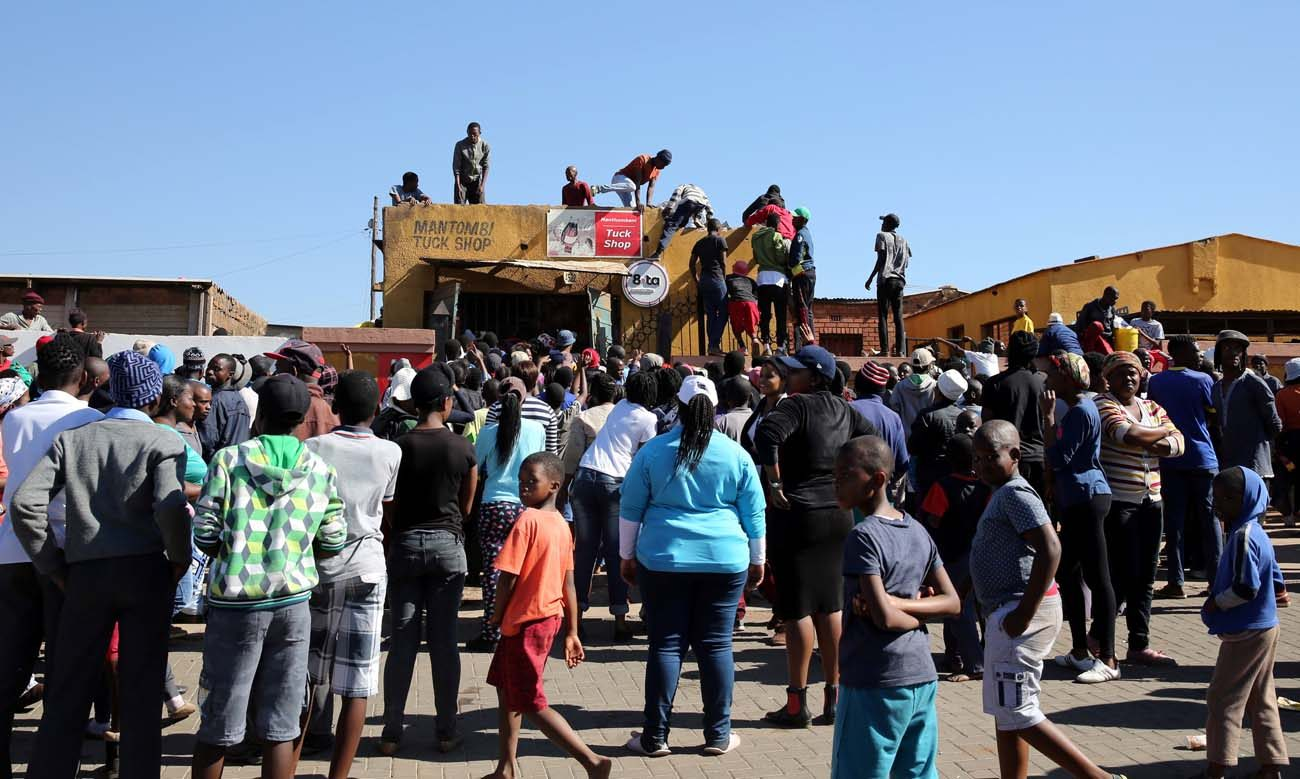 Looters climb on the roofs of shops during protests in Pretoria, South Africa, June 21. South African church leaders have urged an end to pre-election violence and criticized politicians for fueling it. (CNS photo/Siphiwe Sibeko, Reuters)