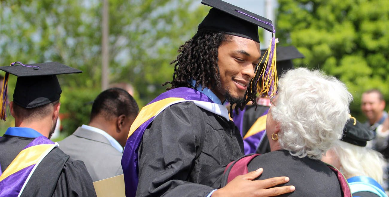 Christian Johnson embraces professor Peggy Tillman after St. Catharine College's graduation ceremony May 14 in Springfield, Ky. (CNS photo/courtesy St. Catharine College)